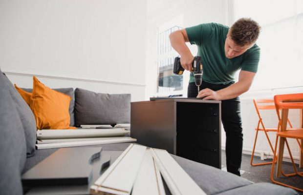 Young man putting up flat pack furniture in his new home.